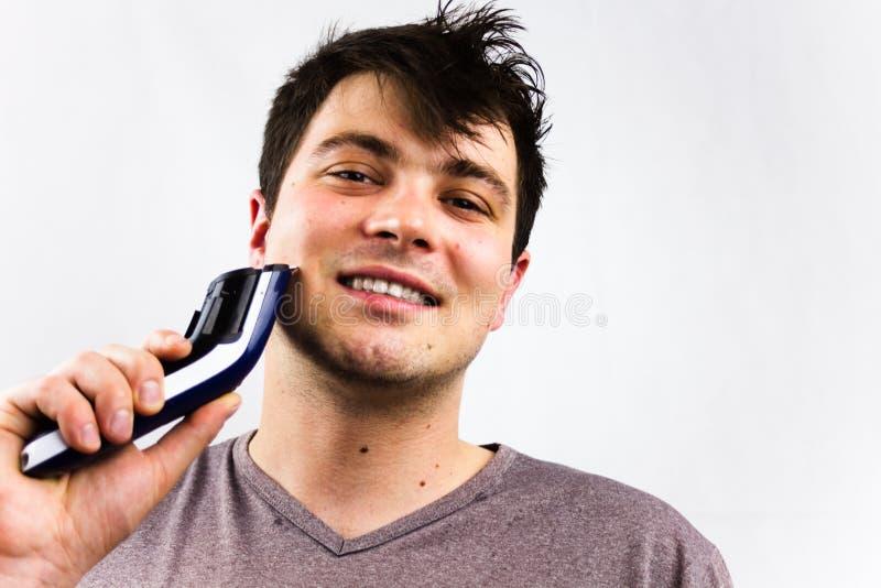 Glimlachende jonge mens die scheerapparaat voor spiegel met behulp van Schoonheid, het verzorgen en mensenconcept Knappe mens die royalty-vrije stock fotografie