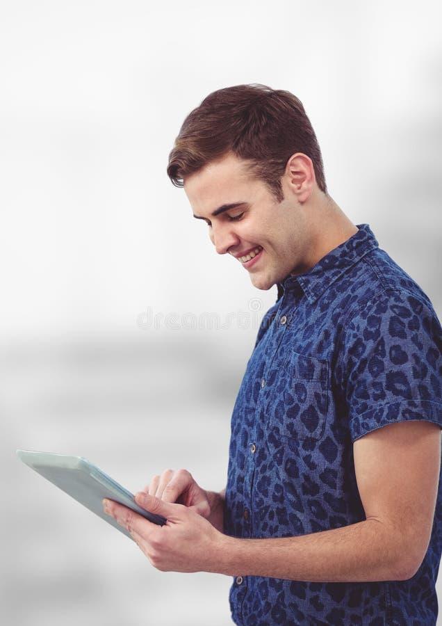 Glimlachende jonge mens die tabletpc met behulp van stock foto