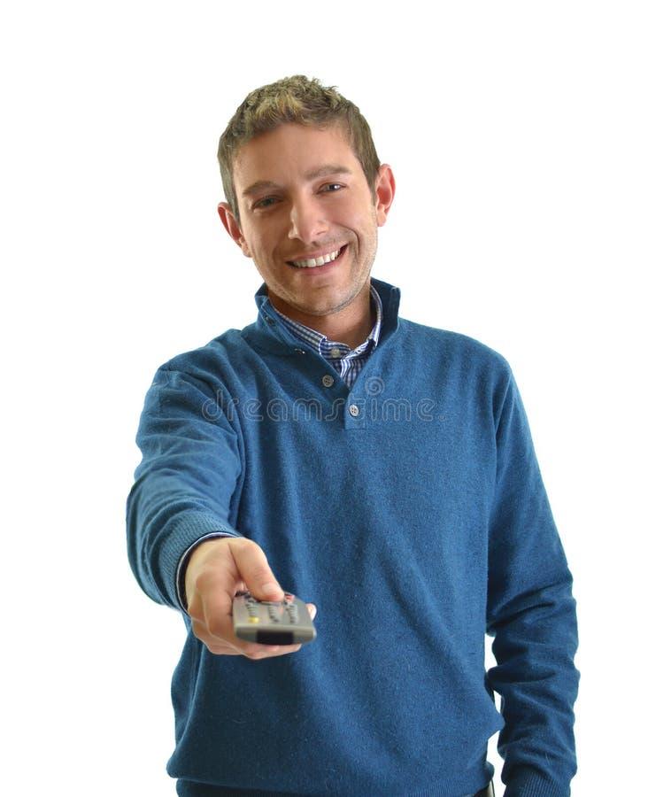 Glimlachende jonge mens die TV-afstandsbediening richten stock fotografie