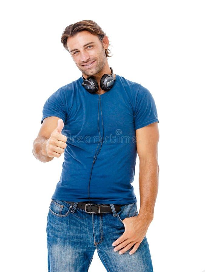 Glimlachende jonge mens die u de duimen opgeven stock afbeelding