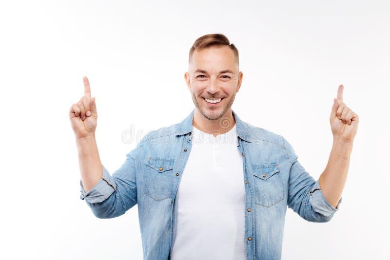 Glimlachende jonge mens die vingers benadrukken stock foto