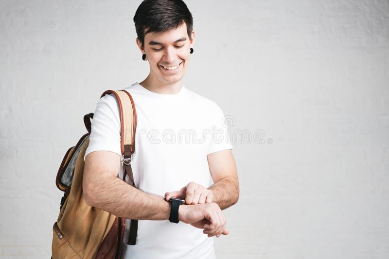 Glimlachende jonge mens die witte t-shirt dragen en packpack stock foto