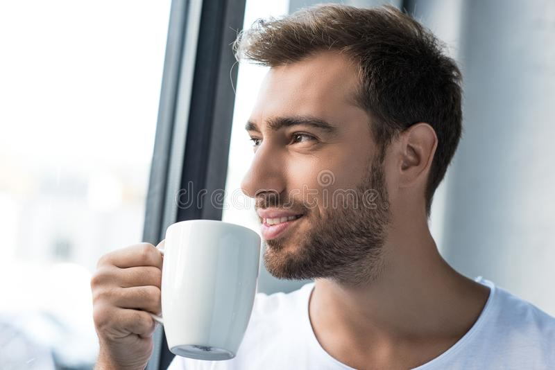 Glimlachende jonge mens die witte t-shirt dragen die zich door het venster met kop bevinden royalty-vrije stock foto's