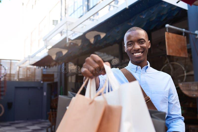 Glimlachende jonge mens die zich buiten het steunen van het winkelen zakken bevinden stock foto
