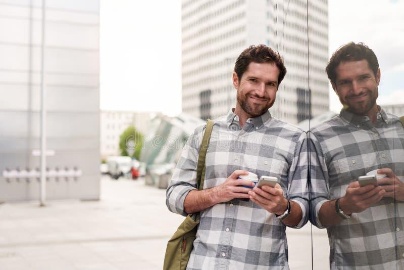 Glimlachende jonge mens die zich in de stad bevinden die zijn cellphone gebruiken stock afbeelding