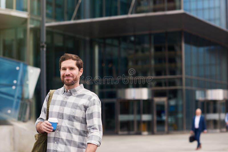 Glimlachende jonge mens die zich in de stad het drinken koffie bevinden stock foto