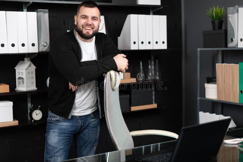 Glimlachende jonge mens die zich dichtbij hoge stoel in bureau bevinden royalty-vrije stock foto's
