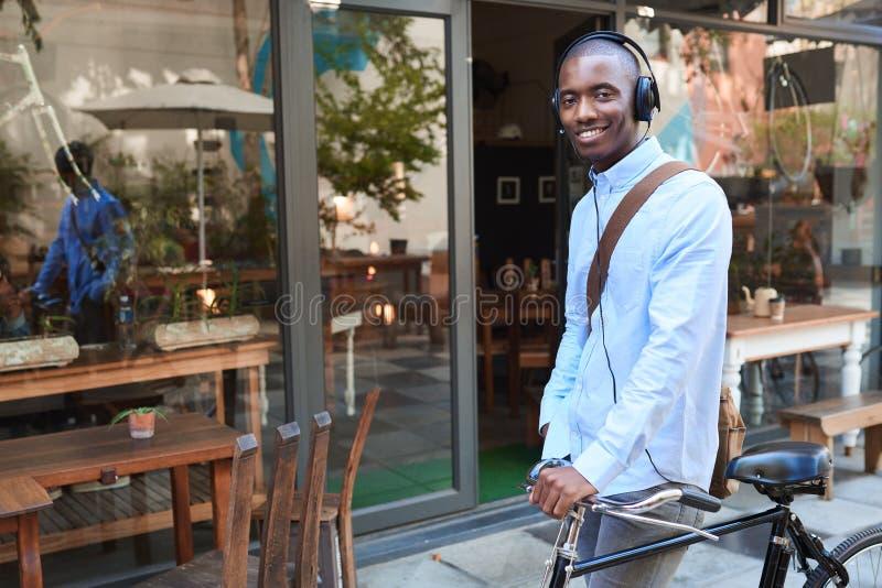 Glimlachende jonge mens die zich met zijn fiets bevinden die hoofdtelefoons dragen stock afbeelding