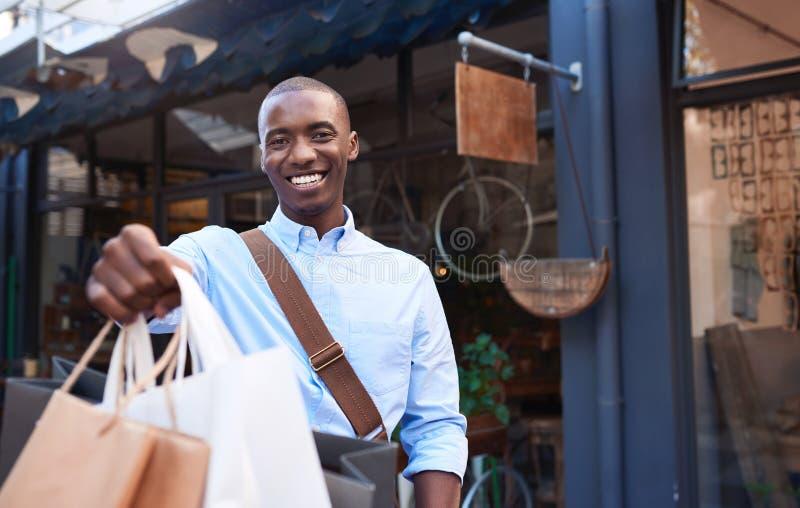 Glimlachende jonge mens die zich op de straatholding het winkelen zakken bevinden royalty-vrije stock afbeelding