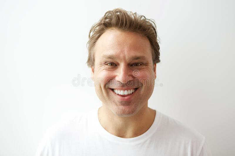 Glimlachende jonge mens die zich tegen witte muur bevinden royalty-vrije stock afbeeldingen