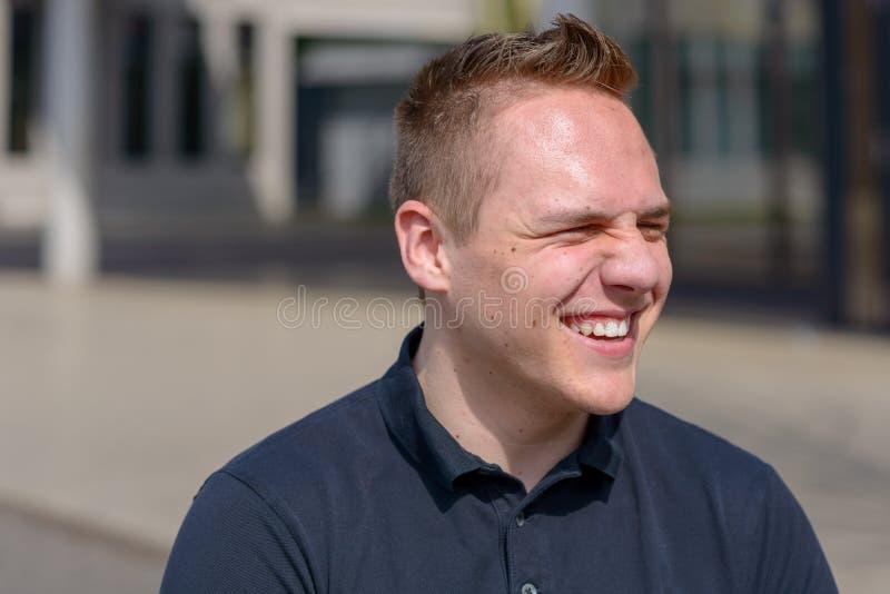 Glimlachende jonge mens die zijn ogen verknoeien stock fotografie
