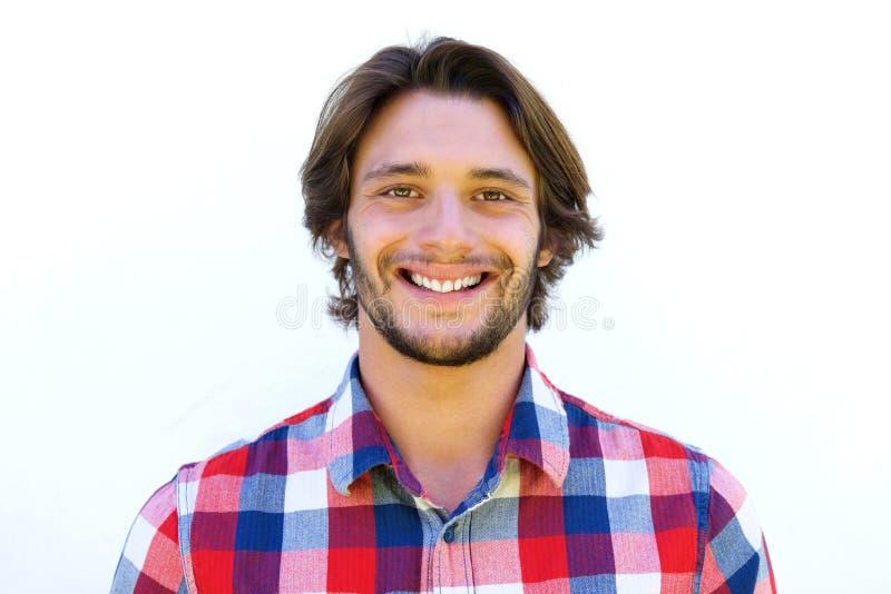 Glimlachende jonge mens met baard die zich tegen witte achtergrond bevinden stock afbeeldingen