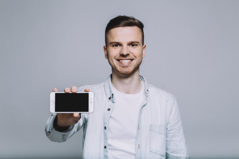 Glimlachende jonge mens met baard in een wit overhemd royalty-vrije stock foto's