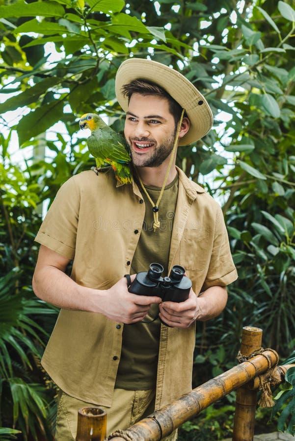 glimlachende jonge mens met papegaai op schouder en verrekijkers stock foto's