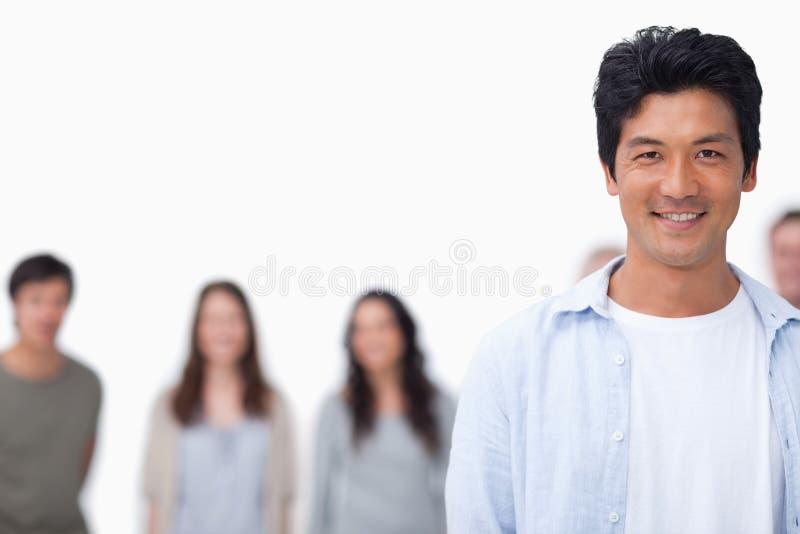 Glimlachende jonge mens met vrienden die zich achter hem bevinden stock foto's