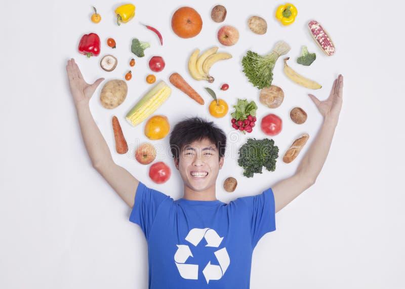 Glimlachende jonge mens met wapens uitgestrekt en vers fruit en groenten rond zijn hoofd, studioschot stock afbeeldingen