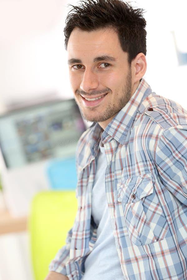 Glimlachende jonge mens op kantoor stock afbeelding