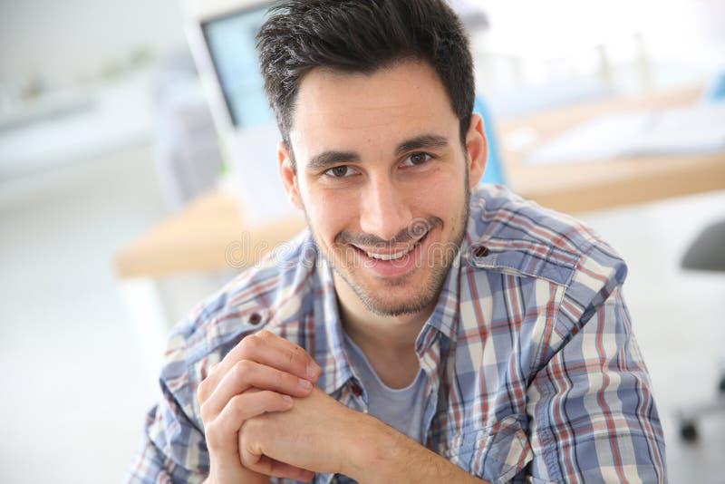 Glimlachende jonge mens op kantoor royalty-vrije stock afbeelding