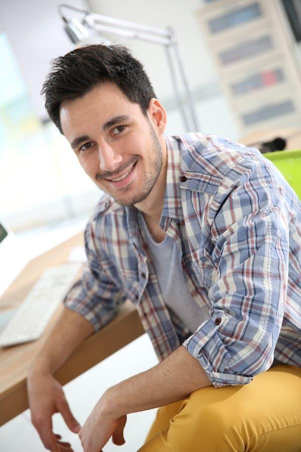 Glimlachende jonge mens op kantoor stock fotografie
