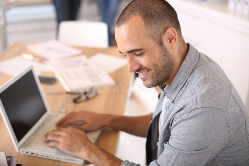 Glimlachende jonge mens op kantoor die aan laptop werken royalty-vrije stock foto's