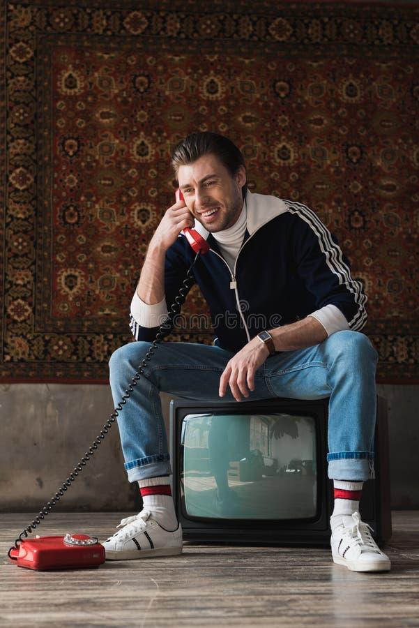 glimlachende jonge mens in uitstekende kleren die op retro TV-reeks zitten en telefonisch voor deken het hangen spreken stock afbeelding