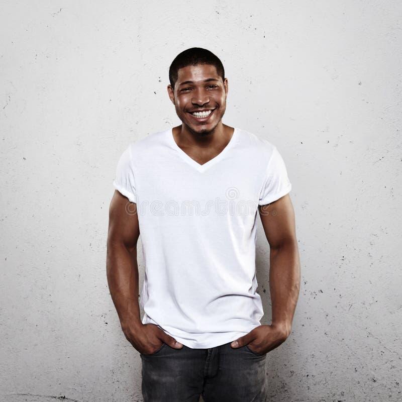 Glimlachende jonge mens in witte t-shirt royalty-vrije stock afbeeldingen