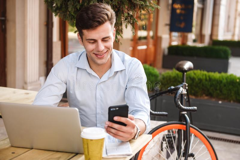 Glimlachende jonge modieuze mens in overhemd die mobiele telefoon met behulp van royalty-vrije stock foto