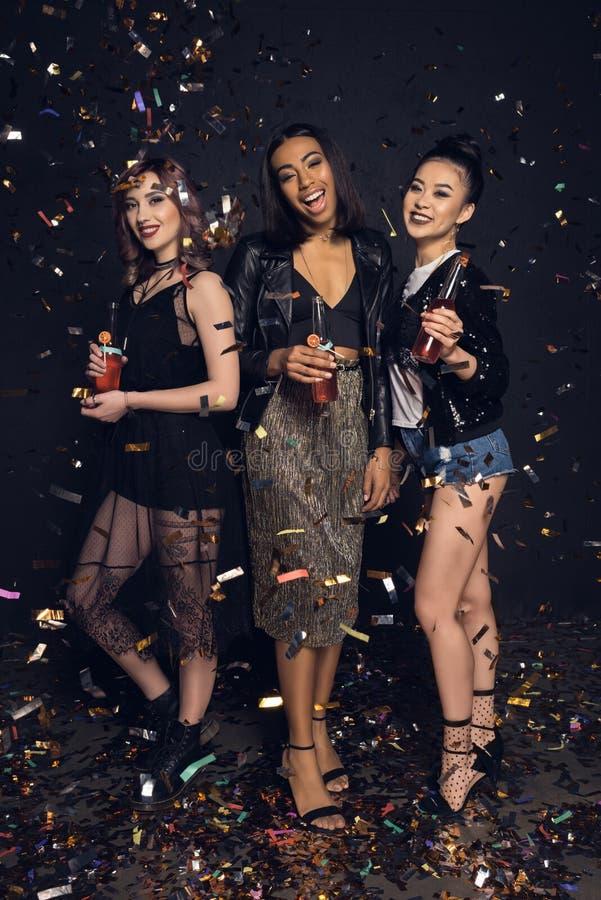 Glimlachende jonge modieuze vrouwen die flessen en het partying houden stock afbeelding