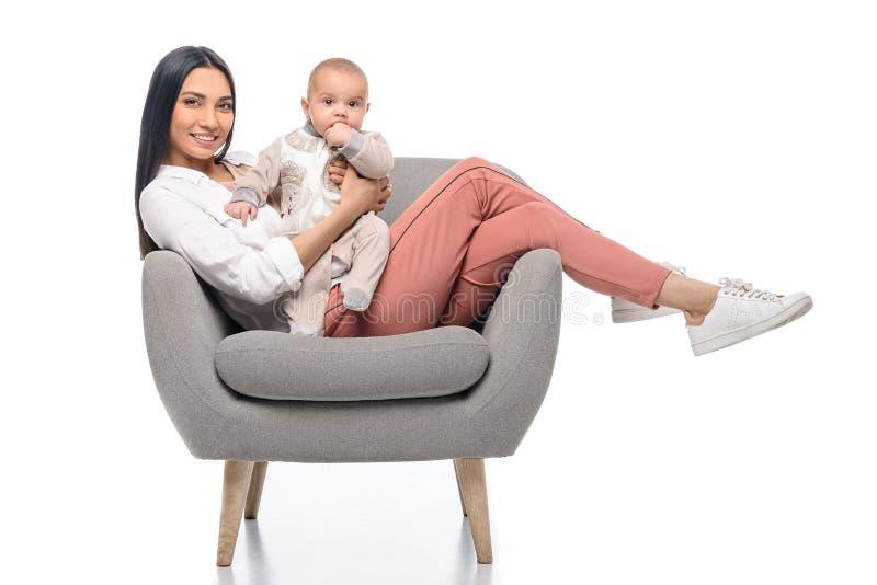 glimlachende jonge moeder die op wapenstoel rusten samen met weinig baby stock afbeeldingen