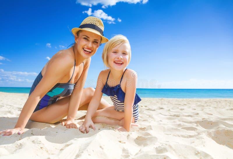 Glimlachende jonge moeder en dochter in swimwear op zeekust royalty-vrije stock afbeeldingen