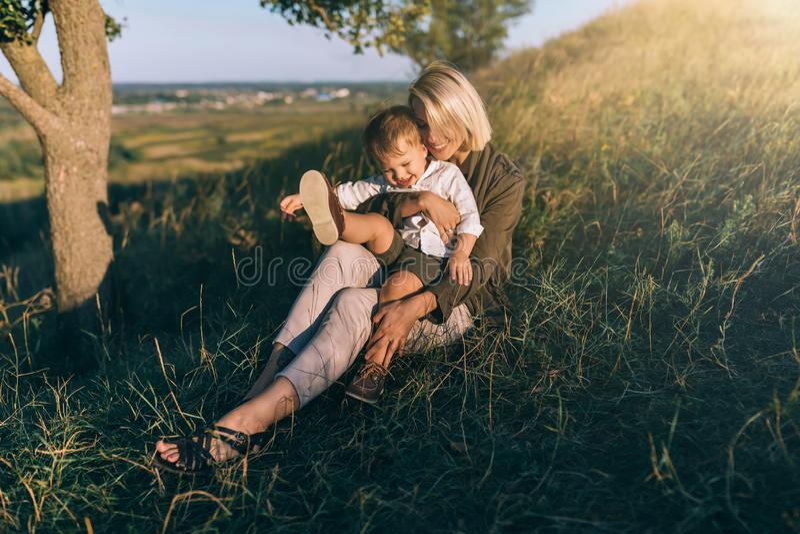 glimlachende jonge moeder en leuk weinig zoonszitting samen op groen gras royalty-vrije stock afbeelding