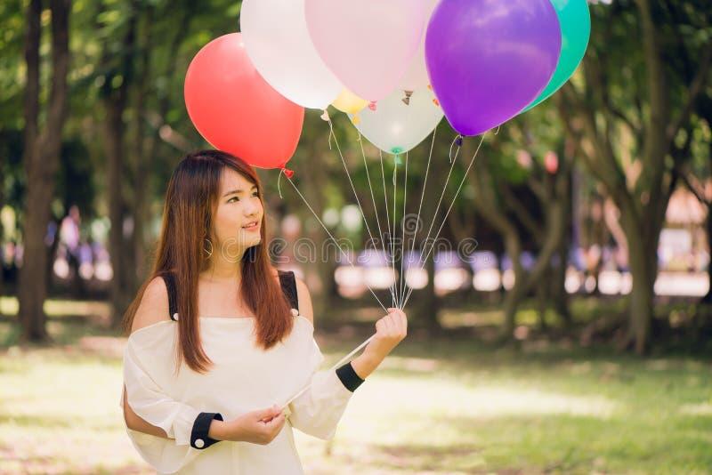 Glimlachende jonge mooie Aziatische vrouwen met lang bruin haar in het park Met regenboog-gekleurde luchtballons stock fotografie