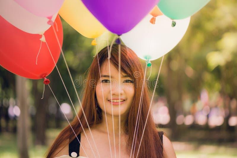Glimlachende jonge mooie Aziatische vrouwen met lang bruin haar in het park Met regenboog-gekleurde luchtballons stock foto