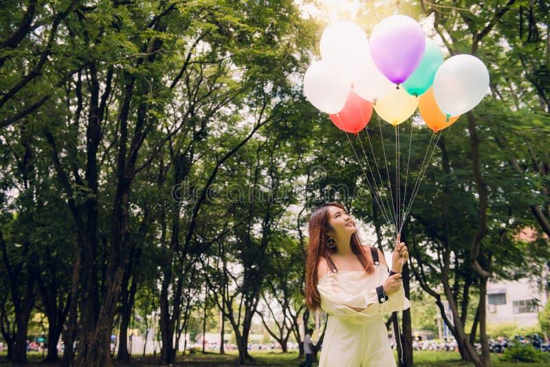 Glimlachende jonge mooie Aziatische vrouwen met lang bruin haar in het park Met regenboog-gekleurde luchtballons royalty-vrije stock foto