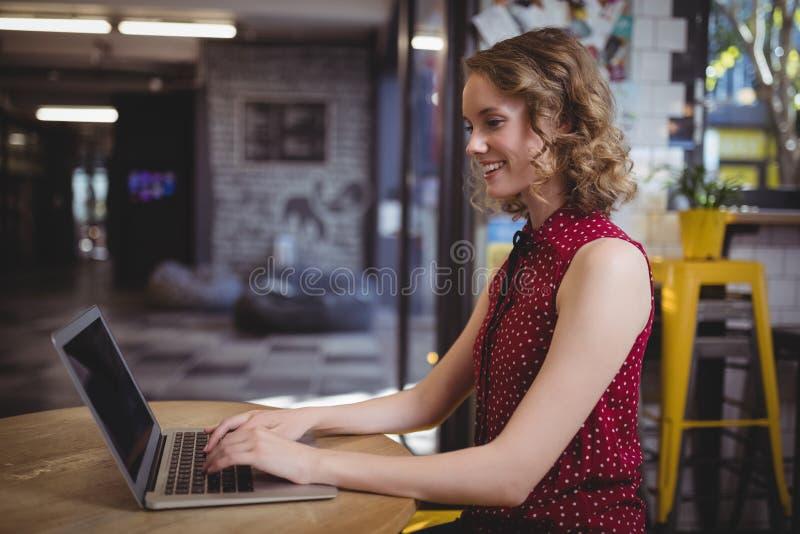 Glimlachende jonge mooie vrouwelijke klant die laptop met behulp van bij lijst royalty-vrije stock foto's