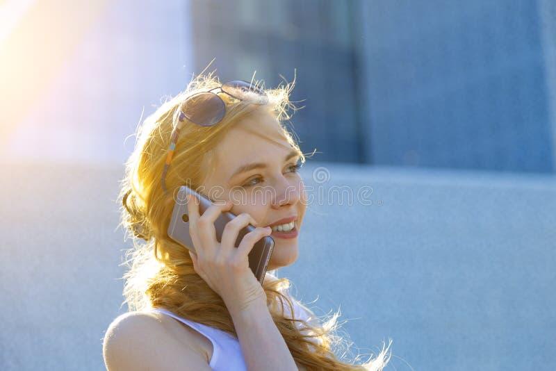 Glimlachende jonge onderneemster die haar vriend roepen terwijl het lopen naar huis van het werk in moderne stad De gouden strale royalty-vrije stock foto's