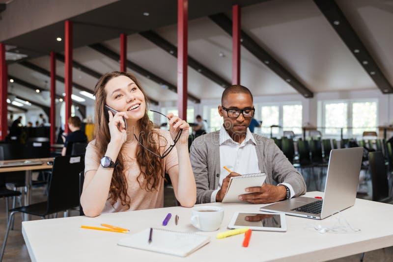 Glimlachende jonge onderneemster die op mobiele telefoon in bureau spreken royalty-vrije stock foto's
