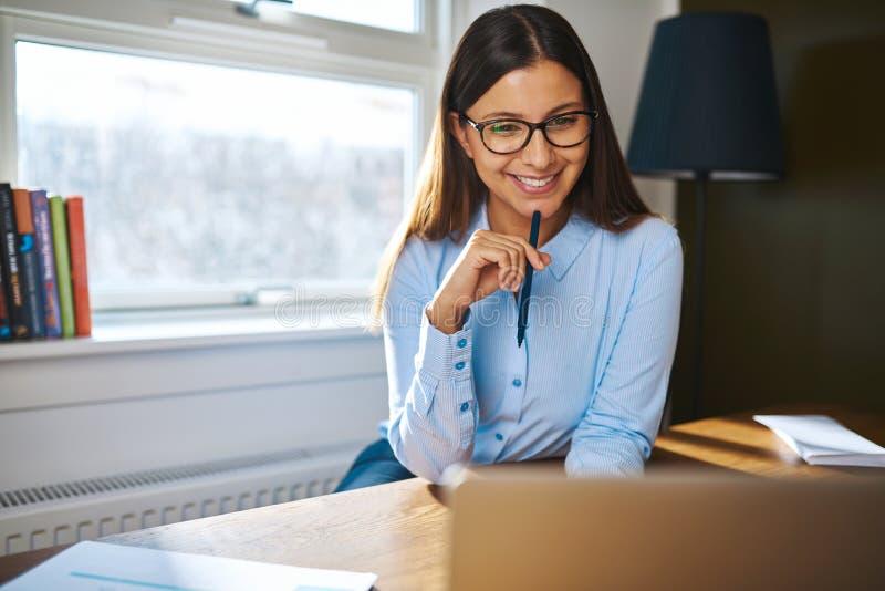 Glimlachende jonge onderneemster die thuis werken stock afbeelding