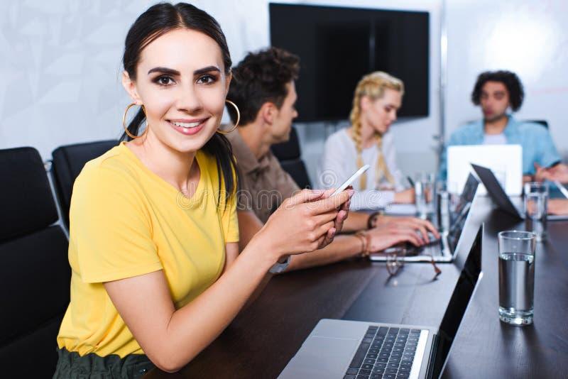 glimlachende jonge onderneemster met smartphone en haar partners die bespreking hebben erachter bij modern stock afbeeldingen