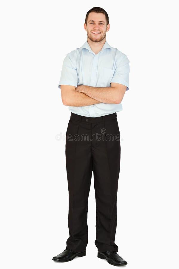 Glimlachende jonge postwerknemer met gevouwen wapens stock afbeelding