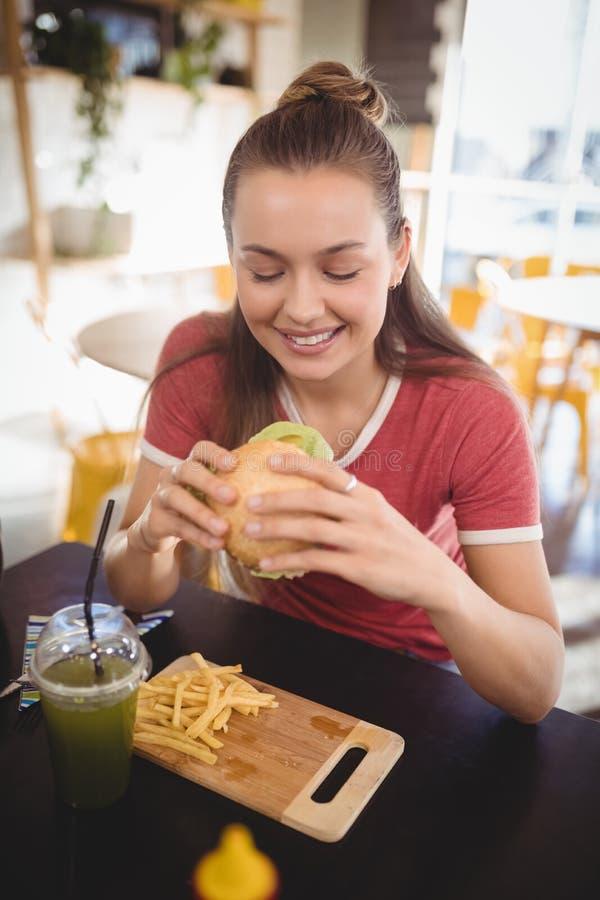 Glimlachende jonge schitterende vrouw die hamburger eten bij koffiewinkel stock fotografie