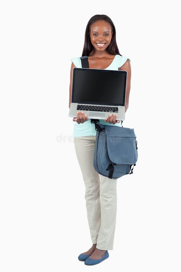 Glimlachende jonge student die haar laptop toont stock afbeeldingen