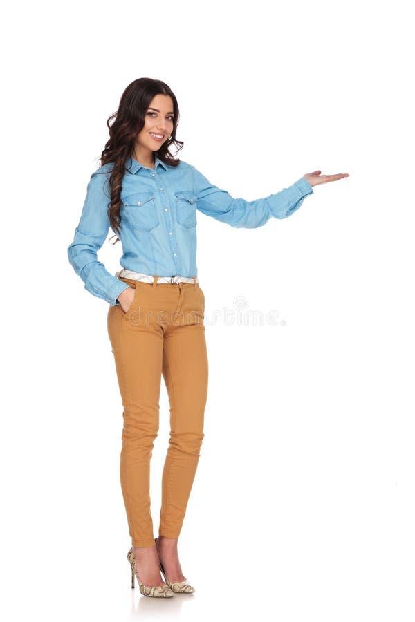 Glimlachende jonge studente die met haar palm aan kant voorstellen royalty-vrije stock afbeelding