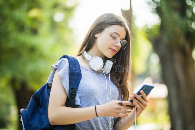 Glimlachende jonge studente die met rugzak mobiele telefoon met oortelefoons houden, die bij het park lopen royalty-vrije stock foto