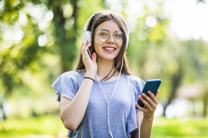 Glimlachende jonge studente die mobiele telefoon houden, lopend bij het park, die aan muziek met oortelefoons luisteren royalty-vrije stock afbeeldingen