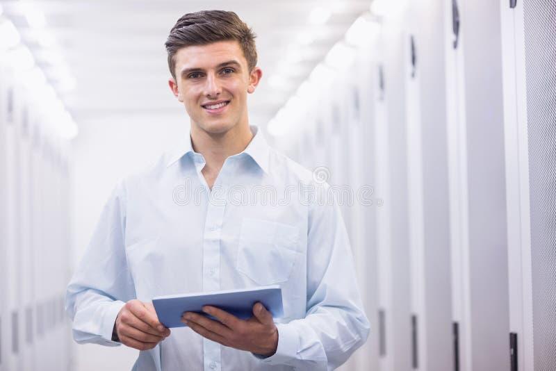 Glimlachende jonge technicus die met zijn tablet werken royalty-vrije stock fotografie