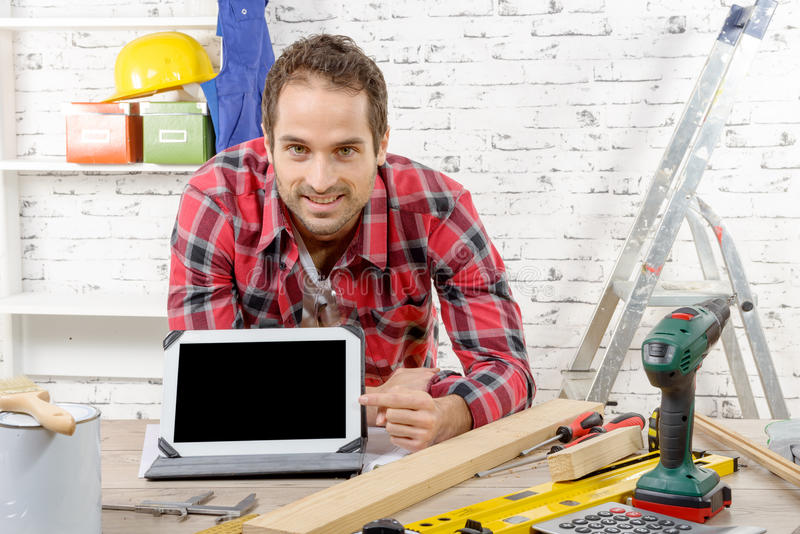Glimlachende jonge timmerman die het scherm op digitale tablet tonen royalty-vrije stock foto