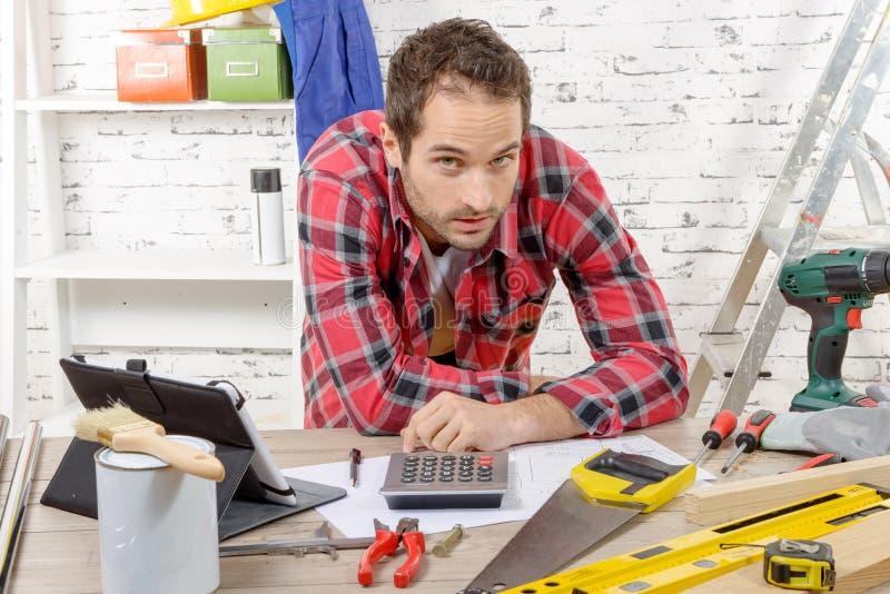 Glimlachende jonge timmerman in zijn workshop stock afbeeldingen