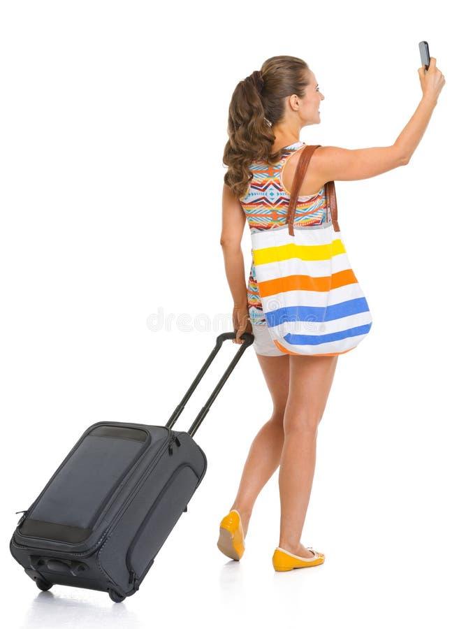 Glimlachende toeristenvrouw met wielzak die foto neemt stock fotografie