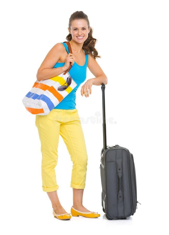 Glimlachende jonge toeristenvrouw met wielzak royalty-vrije stock foto's